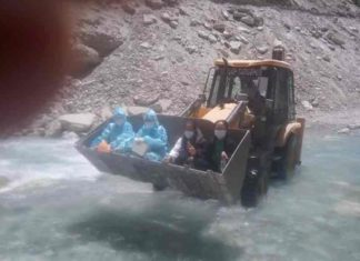 Health workers sitting on JCB 'hands' across river